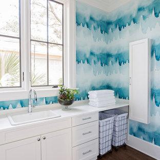 Aménagement d'une buanderie linéaire bord de mer dédiée avec un évier posé, un placard à porte shaker, des portes de placard blanches, un mur bleu, un sol en bois foncé, un sol marron, un plan de travail blanc et du papier peint.