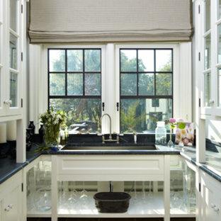 Inredning av ett mellanstort parallellt grovkök, med en undermonterad diskho, luckor med glaspanel, vita skåp, marmorbänkskiva, vita väggar och klinkergolv i keramik