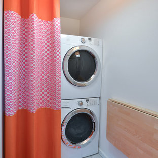 Example of a coastal single-wall laundry room design in Charleston with white walls and a stacked washer/dryer
