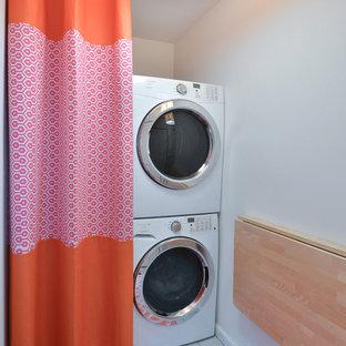 Immagine di una lavanderia costiera con pareti bianche e lavatrice e asciugatrice a colonna