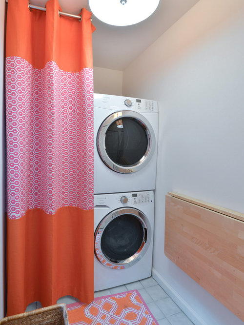 example of a coastal singlewall laundry room design in charleston with white walls and