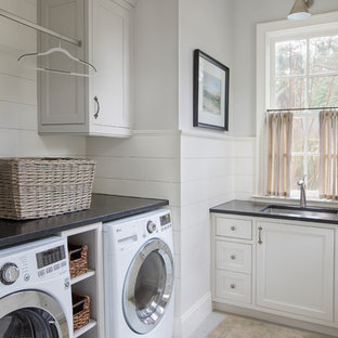Inspiration for a nautical separated utility room in Charleston with a submerged sink, beaded cabinets, white cabinets, a side by side washer and dryer, grey floors and black worktops.