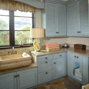 Cette photo montre une buanderie bord de mer en L de taille moyenne avec des portes de placard bleues, un placard à porte persienne, un mur beige, un évier 1 bac, un plan de travail en calcaire, un sol en calcaire et un plan de travail beige.