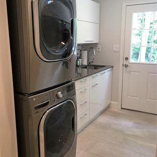 Foto di una piccola sala lavanderia chic con lavello sottopiano, ante lisce, ante bianche, top in quarzo composito, pareti grigie, parquet chiaro, lavatrice e asciugatrice a colonna, pavimento marrone e top grigio