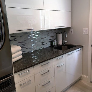 Small traditional single-wall separated utility room in Philadelphia with a submerged sink, flat-panel cabinets, white cabinets, engineered stone countertops, grey walls, light hardwood flooring, a stacked washer and dryer and black worktops.