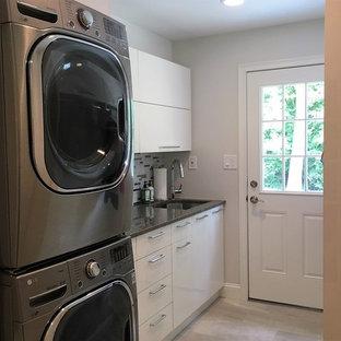 Immagine di una piccola sala lavanderia tradizionale con lavello sottopiano, ante lisce, ante bianche, top in quarzo composito, pareti grigie, parquet chiaro, lavatrice e asciugatrice a colonna e top grigio