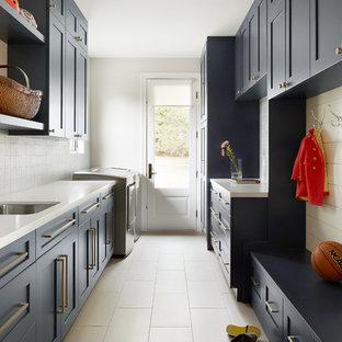 Idee per una lavanderia multiuso stile marinaro con lavello sottopiano, ante in stile shaker, ante blu, pareti grigie, lavatrice e asciugatrice affiancate, pavimento beige e top bianco