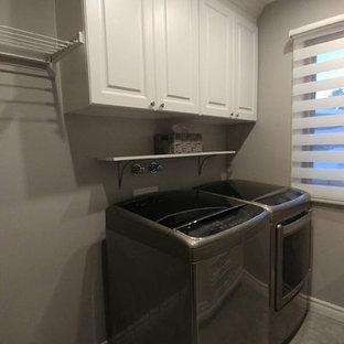 Esempio di una piccola lavanderia multiuso classica con lavello a vasca singola, ante con bugna sagomata, ante bianche, top in quarzite, pareti grigie, pavimento in vinile, lavatrice e asciugatrice affiancate, pavimento grigio e top grigio