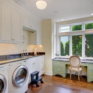 Immagine di una piccola lavanderia multiuso classica con ante bianche, ante con riquadro incassato, pareti bianche, pavimento in legno massello medio e lavello sottopiano