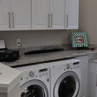 Klassisk inredning av en liten grå linjär grått liten tvättstuga, med luckor med upphöjd panel, gula skåp, granitbänkskiva, grå väggar, mellanmörkt trägolv, en tvättmaskin och torktumlare bredvid varandra och brunt golv