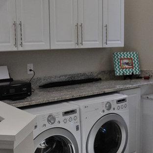 Inspiration för små klassiska linjära grått små tvättstugor, med luckor med upphöjd panel, gula skåp, granitbänkskiva, grå väggar, mellanmörkt trägolv, en tvättmaskin och torktumlare bredvid varandra och brunt golv