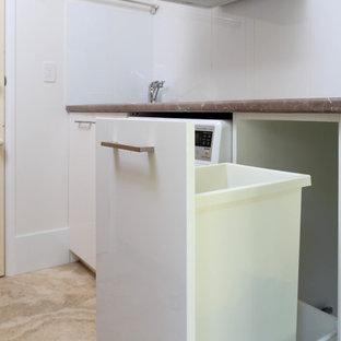 Inspiration för en liten funkis grå l-formad grått liten tvättstuga med garderob, med en undermonterad diskho, släta luckor, vita skåp, bänkskiva i kvarts, grå väggar, klinkergolv i porslin och vitt golv