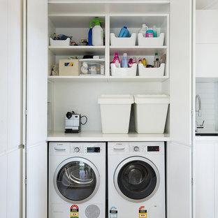 Esempio di un ripostiglio-lavanderia contemporaneo con lavello sottopiano, ante lisce, ante bianche, pareti bianche, pavimento in legno massello medio, lavatrice e asciugatrice affiancate, pavimento marrone e top bianco