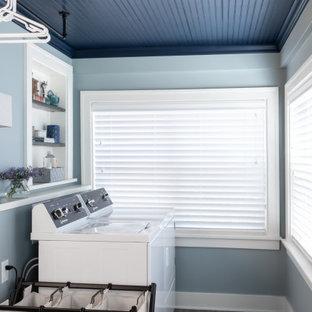 Inredning av ett klassiskt linjärt grovkök, med blå väggar, klinkergolv i porslin, en tvättmaskin och torktumlare bredvid varandra och brunt golv