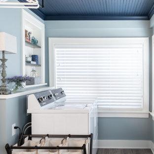 Cette photo montre une buanderie linéaire chic multi-usage avec un mur bleu, un sol en carrelage de porcelaine, des machines côte à côte, un sol marron, un plafond en bois et du lambris.