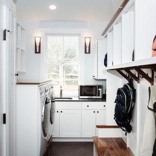 Пример оригинального дизайна: угловая универсальная комната среднего размера в классическом стиле с врезной раковиной, фасадами в стиле шейкер, белыми фасадами, столешницей из талькохлорита, синими стенами, полом из керамогранита, со стиральной и сушильной машиной рядом, коричневым полом и черной столешницей