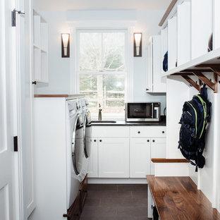 Idéer för att renovera ett mellanstort vintage svart l-format svart grovkök, med en undermonterad diskho, skåp i shakerstil, vita skåp, bänkskiva i täljsten, blå väggar, klinkergolv i porslin, en tvättmaskin och torktumlare bredvid varandra och brunt golv