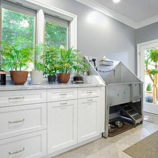 Inredning av ett klassiskt mellanstort grå linjärt grått grovkök, med luckor med infälld panel, vita skåp, marmorbänkskiva, grå väggar och beiget golv