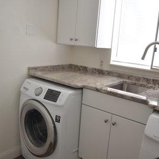 Idéer för små funkis linjära tvättstugor enbart för tvätt, med en enkel diskho, släta luckor, vita skåp, granitbänkskiva, plywoodgolv och en tvättmaskin och torktumlare bredvid varandra
