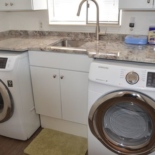 Small contemporary single-wall dedicated laundry room in Detroit with an undermount sink, flat-panel cabinets, white cabinets, granite benchtops, plywood floors and a side-by-side washer and dryer.