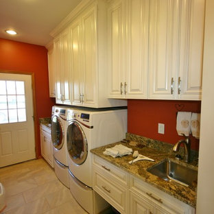 Photo of a small modern single-wall utility room in Milwaukee with an undermount sink, raised-panel cabinets, white cabinets, granite benchtops, beige splashback, stone tile splashback, porcelain floors, red walls and a side-by-side washer and dryer.