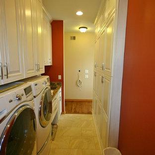 Idéer för små funkis linjära grovkök, med en undermonterad diskho, luckor med upphöjd panel, vita skåp, granitbänkskiva, beige stänkskydd, stänkskydd i stenkakel, klinkergolv i porslin, röda väggar och en tvättmaskin och torktumlare bredvid varandra