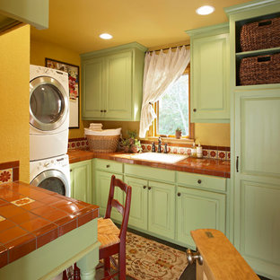 Small classic u-shaped separated utility room in Los Angeles with raised-panel cabinets, green cabinets, tile countertops, yellow walls, a built-in sink, porcelain flooring, a stacked washer and dryer, black floors and red worktops.
