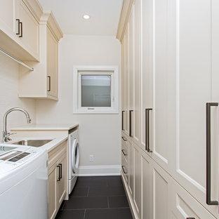 Aménagement d'une buanderie parallèle classique dédiée et de taille moyenne avec un évier encastré, un placard avec porte à panneau encastré, des portes de placard beiges, un mur beige, un sol en carrelage de porcelaine, des machines côte à côte, un sol noir et un plan de travail beige.