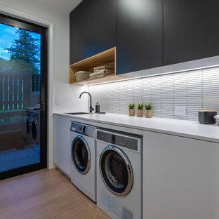 Idee per una lavanderia design con lavello sottopiano, ante bianche, top in quarzo composito, paraspruzzi bianco, paraspruzzi con piastrelle a mosaico, pavimento in laminato, lavatrice e asciugatrice affiancate, top bianco, pareti bianche e pavimento marrone