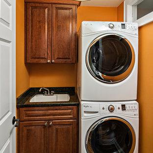 Immagine di una piccola sala lavanderia american style con lavello sottopiano, ante con bugna sagomata, ante in legno bruno, top in granito, pareti arancioni, pavimento in legno massello medio, lavatrice e asciugatrice a colonna, pavimento marrone e top nero