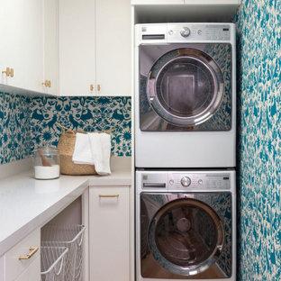 Immagine di una lavanderia boho chic con ante lisce, ante bianche, pareti blu, parquet chiaro, lavatrice e asciugatrice affiancate, pavimento beige e top bianco