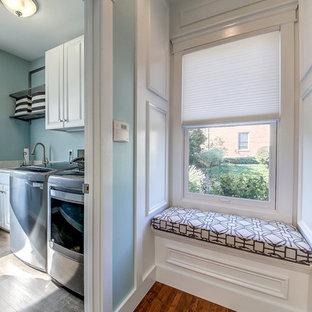 Maritim inredning av en mellanstor grå linjär grått tvättstuga enbart för tvätt, med en undermonterad diskho, luckor med upphöjd panel, vita skåp, granitbänkskiva, blå väggar, vinylgolv, en tvättmaskin och torktumlare bredvid varandra och grått golv