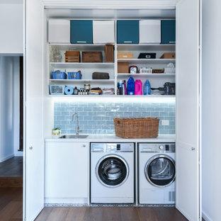 Modern inredning av en vita linjär vitt liten tvättstuga, med en undermonterad diskho, släta luckor, vita skåp, vita väggar, mörkt trägolv, en tvättmaskin och torktumlare bredvid varandra och brunt golv