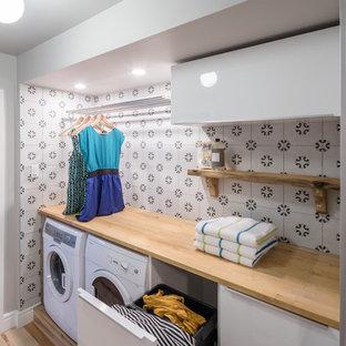 Cette image montre une petit buanderie linéaire design dédiée avec un placard à porte plane, des portes de placard blanches, un plan de travail en bois, un mur gris, un sol en bois clair, des machines côte à côte et un plan de travail beige.