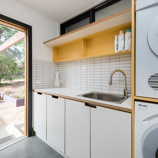 Contemporary single-wall utility room in Canberra - Queanbeyan with a drop-in sink, flat-panel cabinets, white cabinets, white walls, concrete floors, a stacked washer and dryer, grey floor and white benchtop.