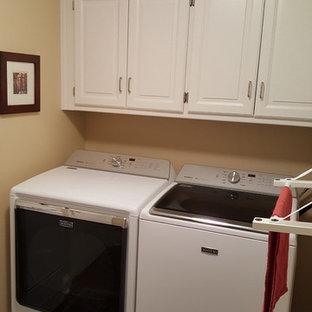 Esempio di una piccola sala lavanderia classica con ante con bugna sagomata, ante bianche, pareti beige, moquette e lavatrice e asciugatrice affiancate