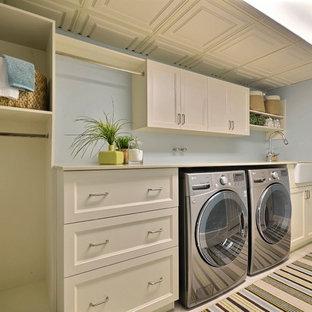 Foto di una grande sala lavanderia chic con ante beige, lavello stile country, pareti blu, pavimento in gres porcellanato, ante in stile shaker, top in quarzo composito, lavatrice e asciugatrice affiancate, pavimento beige e top beige