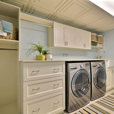Inspiration for a large timeless single-wall porcelain tile and beige floor dedicated laundry room remodel in Montreal with beige cabinets, a farmhouse sink, blue walls, shaker cabinets, quartz countertops, a side-by-side washer/dryer and beige countertops