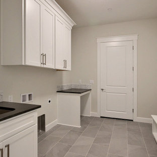 Design ideas for an expansive transitional galley utility room in Portland with an undermount sink, recessed-panel cabinets, white cabinets, quartz benchtops, grey splashback, ceramic splashback, beige walls, ceramic floors, a side-by-side washer and dryer, grey floor and black benchtop.