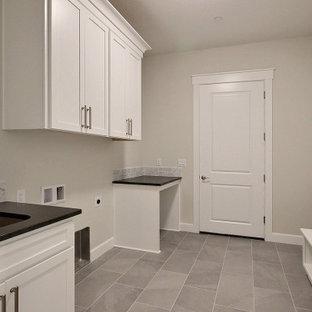 Inredning av ett klassiskt mycket stort svart parallellt svart grovkök, med en undermonterad diskho, luckor med infälld panel, vita skåp, bänkskiva i kvarts, grått stänkskydd, stänkskydd i keramik, beige väggar, klinkergolv i keramik, en tvättmaskin och torktumlare bredvid varandra och grått golv
