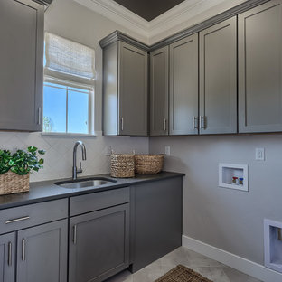 Minimalist l-shaped porcelain floor and beige floor dedicated laundry room photo in Denver with an undermount sink, shaker cabinets, gray cabinets, quartz countertops and white walls