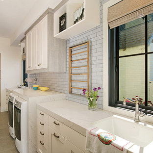 Example of a farmhouse single-wall gray floor dedicated laundry room design in San Diego with an undermount sink, shaker cabinets, white cabinets, white walls, a side-by-side washer/dryer and white countertops