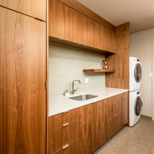 Design ideas for a large midcentury galley dedicated laundry room in Seattle with an undermount sink, flat-panel cabinets, medium wood cabinets, quartz benchtops, green splashback, glass tile splashback, white walls, limestone floors, a stacked washer and dryer, multi-coloured floor and white benchtop.