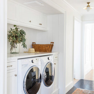 Photo of a farmhouse single-wall laundry cupboard in San Francisco with shaker cabinets, white cabinets, marble worktops, a side by side washer and dryer, black floors and white worktops.