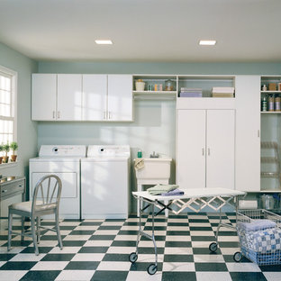 This is an example of a large contemporary single-wall separated utility room in Nashville with an utility sink, flat-panel cabinets, white cabinets, blue walls, lino flooring and a side by side washer and dryer.