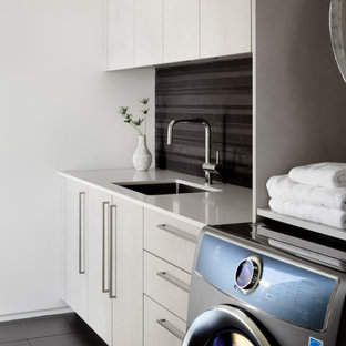 Inspiration pour une buanderie minimaliste avec un évier encastré, un placard à porte plane, des portes de placard grises, un mur noir, des machines côte à côte, un sol noir et un plan de travail blanc.