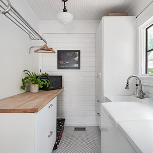 Elegant white floor dedicated laundry room photo in Orlando with an utility sink, flat-panel cabinets, white cabinets, wood countertops and white walls