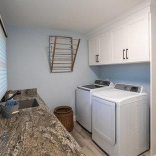 Inspiration för mellanstora klassiska parallella brunt tvättstugor enbart för tvätt, med en undermonterad diskho, luckor med infälld panel, vita skåp, granitbänkskiva, brunt stänkskydd, blå väggar, klinkergolv i porslin, en tvättmaskin och torktumlare bredvid varandra och beiget golv