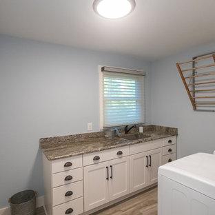 Klassisk inredning av en mellanstor bruna parallell brunt tvättstuga enbart för tvätt, med en undermonterad diskho, luckor med infälld panel, vita skåp, granitbänkskiva, brunt stänkskydd, blå väggar, klinkergolv i porslin, en tvättmaskin och torktumlare bredvid varandra och beiget golv