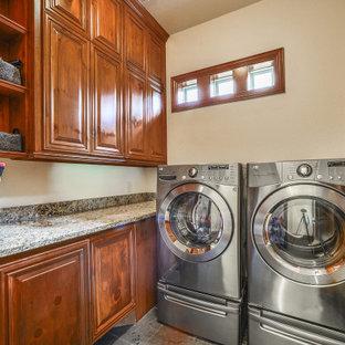 Inredning av en klassisk liten flerfärgade flerfärgat tvättstuga enbart för tvätt, med luckor med upphöjd panel, bruna skåp, bänkskiva i kvarts, grått stänkskydd, klinkergolv i porslin, en tvättmaskin och torktumlare bredvid varandra och grått golv